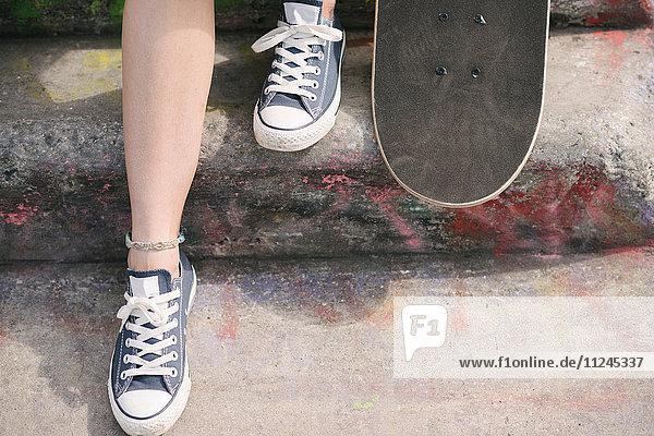 Füße einer Skateboardfahrerin mit Skateboard auf Schritt Füße einer Skateboardfahrerin mit Skateboard auf Schritt