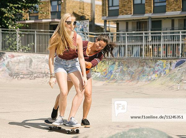 Two women practising skateboarding balance in skatepark