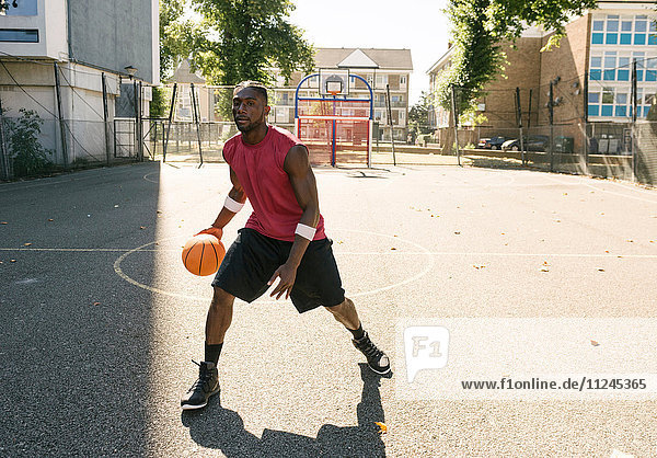 Young man practising on basketball court