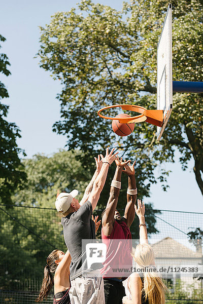 Female and male basketball players throwing ball at basketball hoop