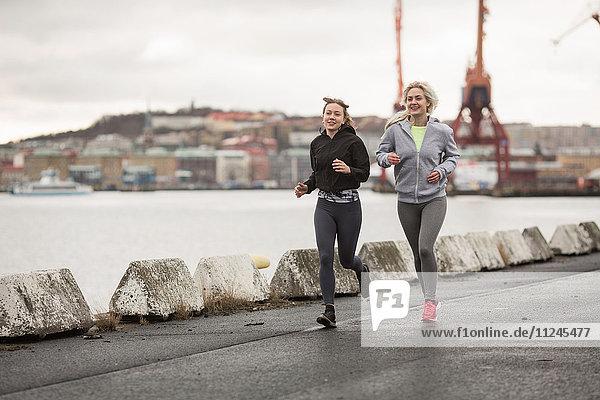 Two female runner friends running along dockside