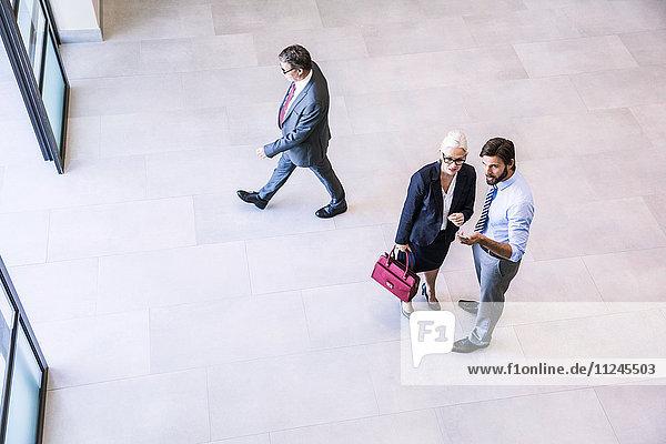 Schrägansicht von zwei Geschäftsleuten,  die eine Geschäftsfrau im Atrium des Büros leiten