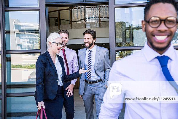 Geschäftsleute unterhalten sich beim Verlassen des Bürogebäudes