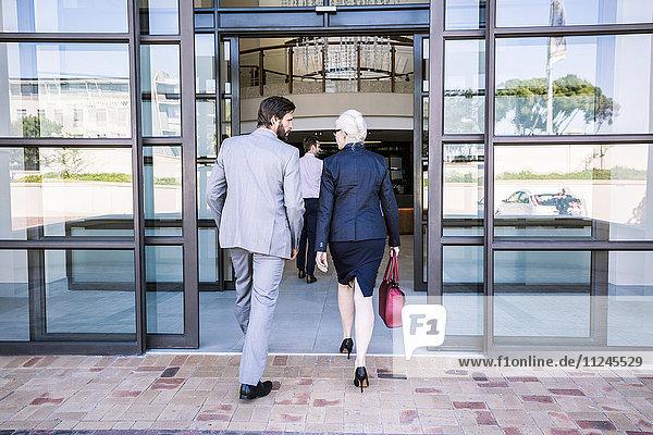 Rückansicht der im Bürogebäude eintreffenden Geschäftsmänner und -frauen