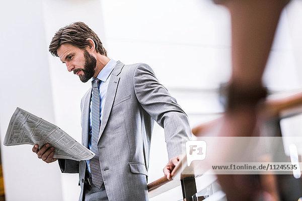 Geschäftsmann liest Zeitung auf Bürobalkon