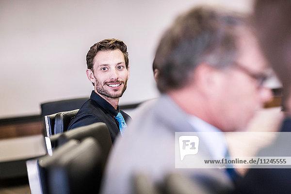 Glücklicher Geschäftsmann in Vorstandssitzung