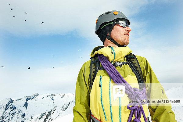 Porträt eines Bergsteigers auf schneebedecktem Berg mit Blick in die Ferne