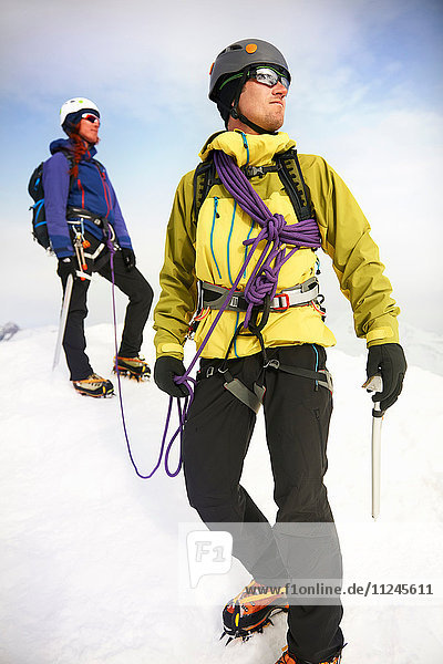 Bergsteiger in schneebedeckter Landschaft schauen weg