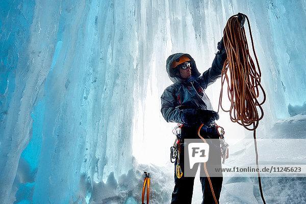 Mann in Eishöhle bereitet Kletterseil vor  Saas Fee  Schweiz