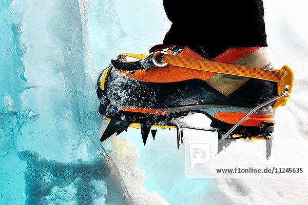 Schrägansicht der Füße von Eiskletterern mit Steigeisen