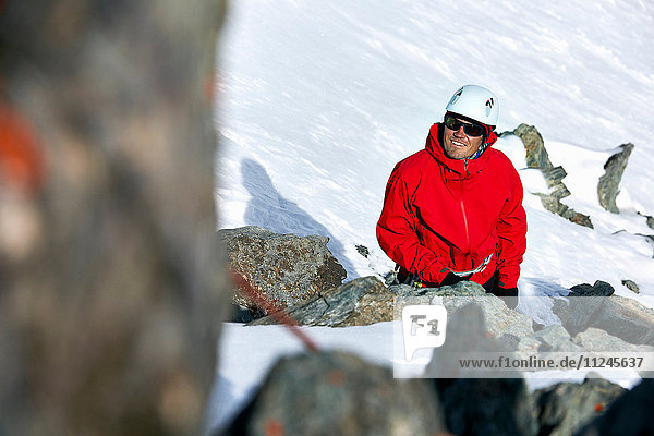 Bergsteiger auf schneebedecktem Berg schaut lächelnd auf  Saas Fee  Schweiz
