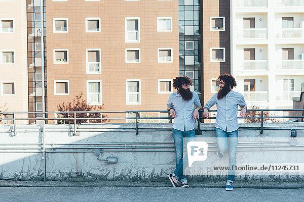 Eineiige männliche-Zwillinge beim Plaudern auf der Dachterrasse der Wohnung Eineiige männliche-Zwillinge beim Plaudern auf der Dachterrasse der Wohnung