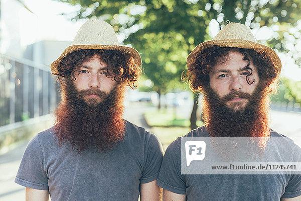 Porträt von eineiigen männlichen Hipster-Zwillingen mit Strohhut auf dem Bürgersteig