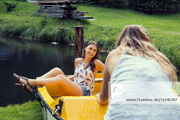 Two young female friends pushing rowing boat at lakeside