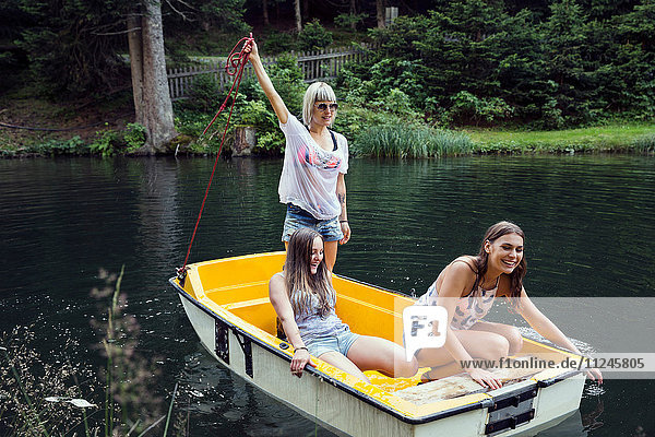 Three adult female friends on rowing boat in lake  Sattelbergalm  Tirol  Austria
