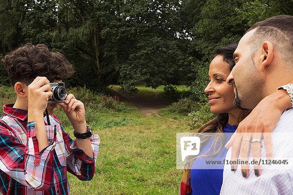 Teenager Junge fotografiert Eltern im Freien mit der Kamera
