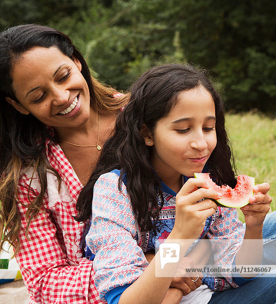 Mother and daughter sitting outdoors  daughter eating watermelon