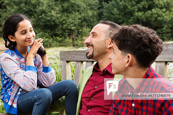 Father sitting on bench with son and daughter  laughing