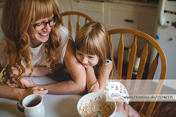 Mother and daughter cuddling at breakfast table