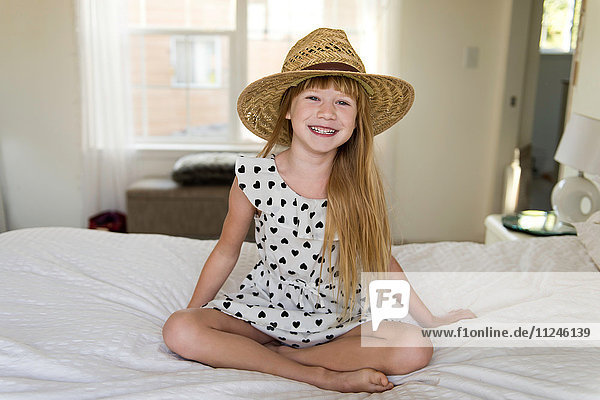 Young girl sitting on bed smiling  wearing straw hat