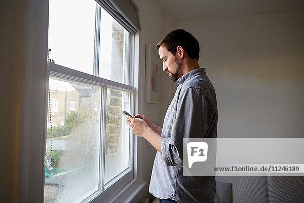Mittlerer Erwachsener Mann am Wohnzimmerfenster beim Lesen von Smartphone-Texten