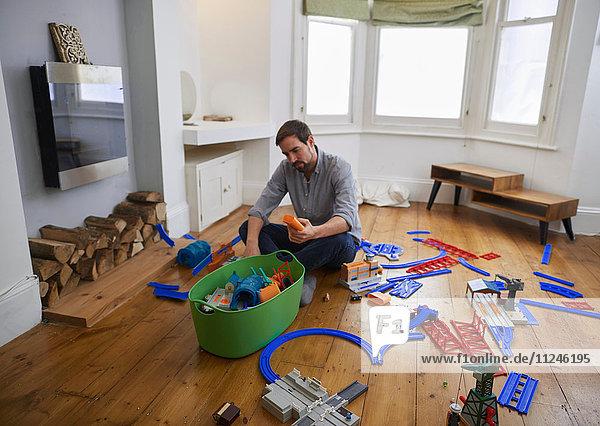 Mittelgroßer erwachsener Mann betrachtet im Wohnzimmer verstreutes Spielzeug