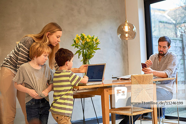 Mid adult woman and sons looking at laptop on dining table
