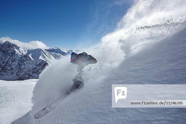 Male freestyle skier skiing down snow powdered mountainside  Zugspitze  Bayern  Germany
