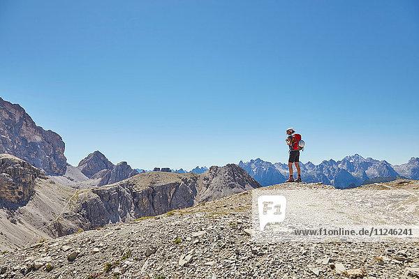 Rückansicht einer Wanderin mit Blick auf die Dolomiten  Sexten  Südtirol  Italien