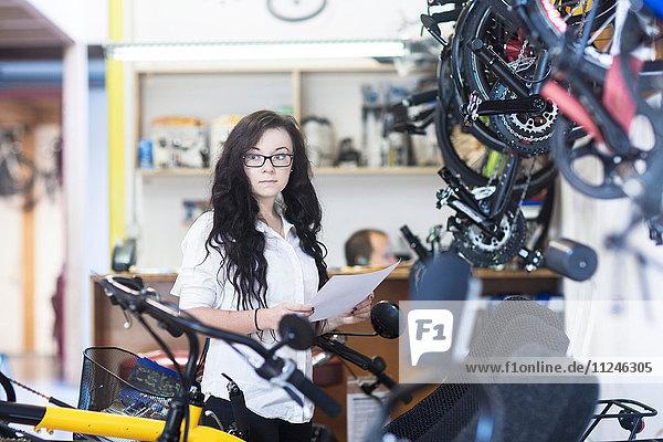 Frau im Fahrradladen mit Papierkram