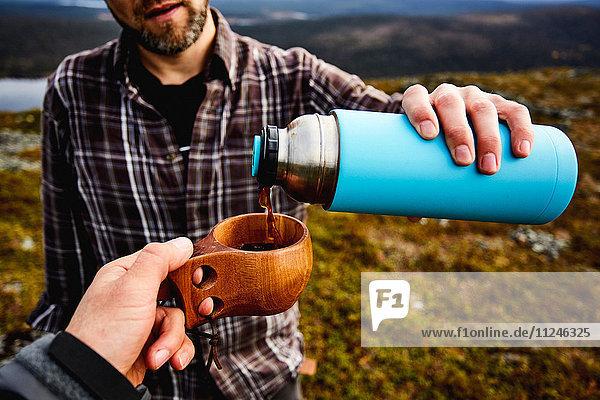Wanderer beim Kaffee trinken auf der Klippe  Keimiotunturi  Lappland  Finnland