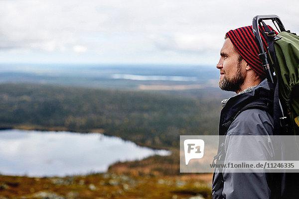 Wanderer geniesst Aussicht auf die Klippen  Keimiotunturi  Lappland  Finnland