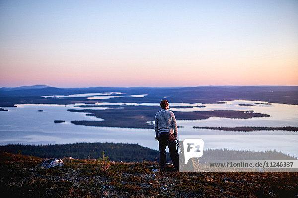 Hiker enjoying sunset at lake  Keimiotunturi  Lapland  Finland
