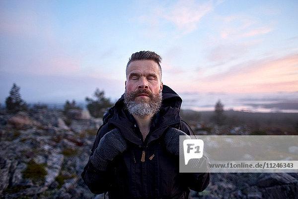 Wanderer genießt die Natur mit geschlossenen Augen  Sarkitunturi  Lappland  Finnland