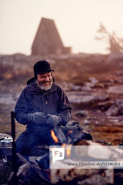 Wanderer lächelnd am Lagerfeuer  Sarkitunturi  Lappland  Finnland