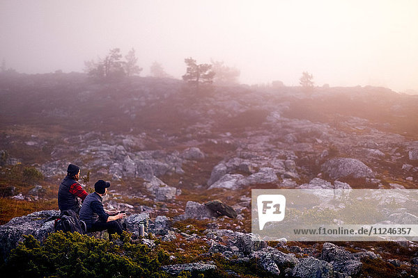 Hikers relaxing with coffee on rocky field  Sarkitunturi  Lapland  Finland