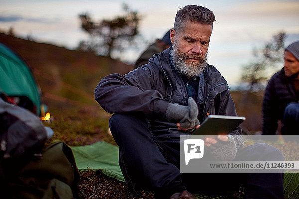 Wanderer mit digitalem Tablett im Zelt  Keimiotunturi  Lappland  Finnland