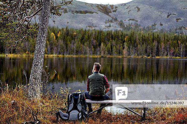 Auf Bank ruhender Wanderer mit Blick auf den See  Kesankijarvi  Lappland  Finnland