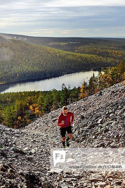 Wanderer  der einen steilen Hügel hinaufläuft  Kesankitunturi  Lappland  Finnland