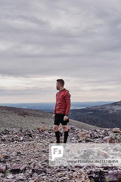 Mann blickt zurück auf felsige Felsspitze  Kesankitunturi  Lappland  Finnland