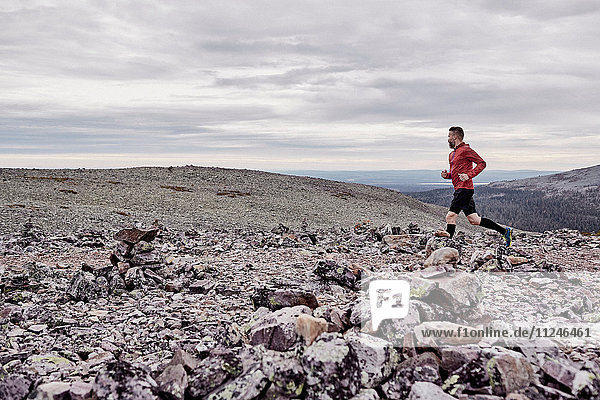 Mann läuft auf felsiger Felsspitze  Kesankitunturi  Lappland  Finnland