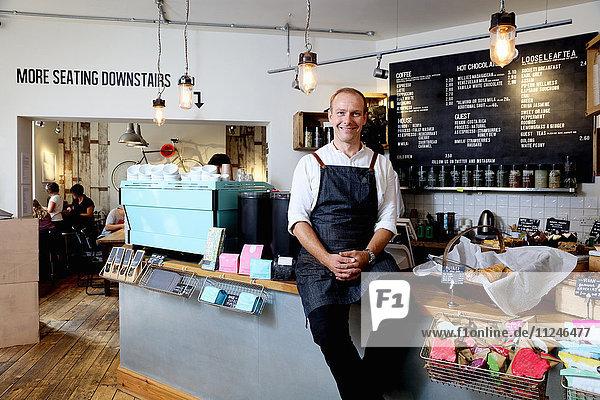 Porträt eines männlichen Geschäftsinhabers  der auf dem Tresen eines unabhängigen Cafés sitzt