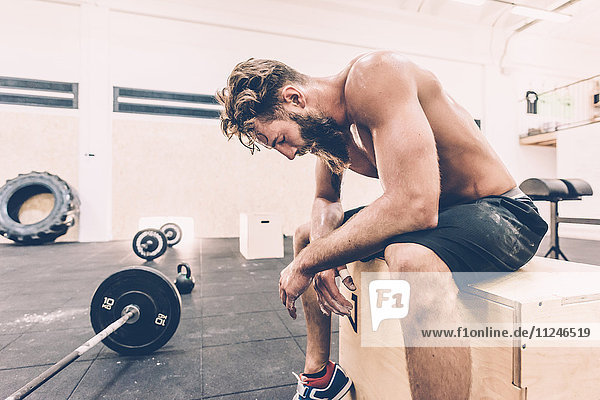 Exhausted male cross trainer taking a break from weightlifting in gym