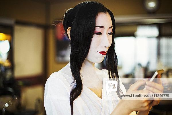 Geisha mit langen schwarzen Haaren und traditionellem weißen Gesichts-Make-up mit einem Smartphone.
