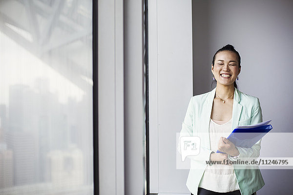 A business woman in the office holding a folder and smiling.