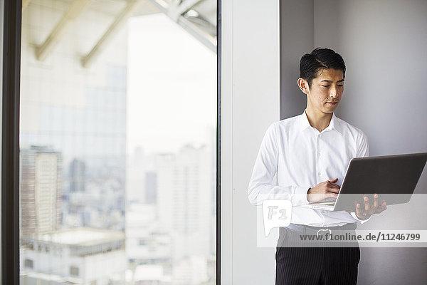 Ein Geschäftsmann  der mit seinem Laptop an einem Fenster mit Blick auf die Stadt steht.