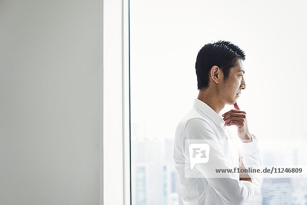 A businessman in the office standing by a large window with arms folded  looking over the city.
