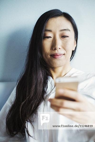 Eine Geschäftsfrau  die sich auf die Arbeit vorbereitet und mit ihrem Smartphone im Bett sitzt.