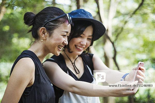 Zwei junge Frauen  die in einem Wald stehen und sich ein Selfie nehmen.