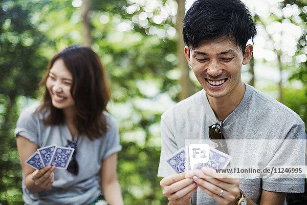 Junge Frau und Mann sitzen in einem Wald und spielen Karten.